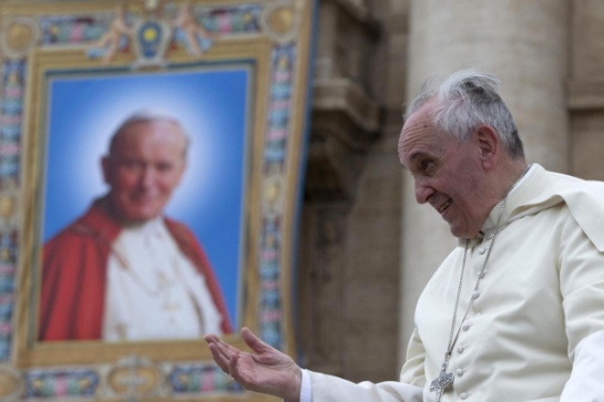 Pope Francis passes by a tapestry depicting late Pope John Paul II as he leaves at the end of his weekly general audience, at the Vatican, Wednesday, April 30, 2014. Francis elevated John Paul II to sainthood during a ceremony in St. Peter's Square last Sunday. (AP Photo/Andrew Medichini)