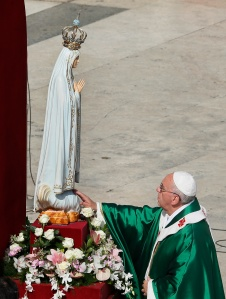 Pope Francis touches the original statue of Our Lady of Fatima after entrusting the world to Mary at the end of a Mass in her honor in St. Peter's Square at the Vatican Oct. 13. (CNS photo/Paul Haring) (Oct. 14, 2013) See POPE-FATIMA Oct. 14, 2013.