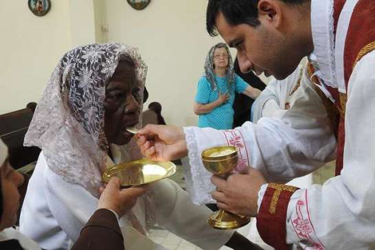 dona_penha_101_receives_first_communion_credit_our_lady_of_mount_carmel_nursing_home_cna_1475500593