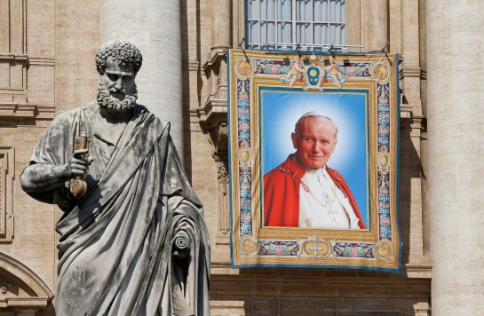 A banner depicting Blessed John Paul II hangs from the facade of St. Peter's Basilica at the Vatican April 25. The banner was hung the morning of April 25 in advance of the April 27 canonization of Blesseds John XXIII and John Paul. At left is a statue of St. Peter. (CNS photo/Paul Haring) (April 25, 2014)